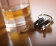 A set of car keys in the foreground and glass of whiskey behind.